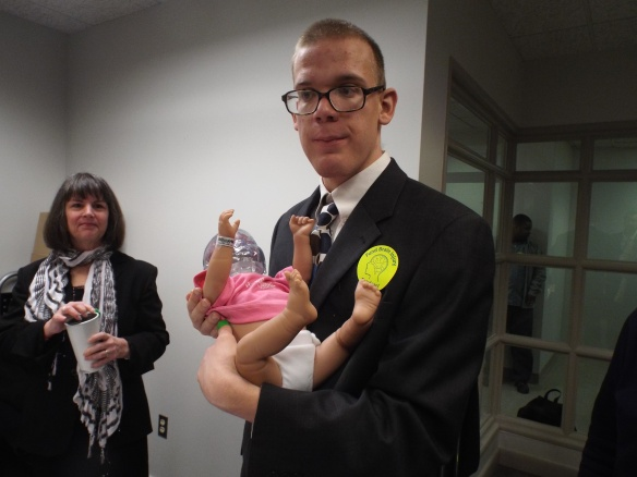 Brandon and a doll that represents Shaken Baby Syndrome. Keeping his head clear!